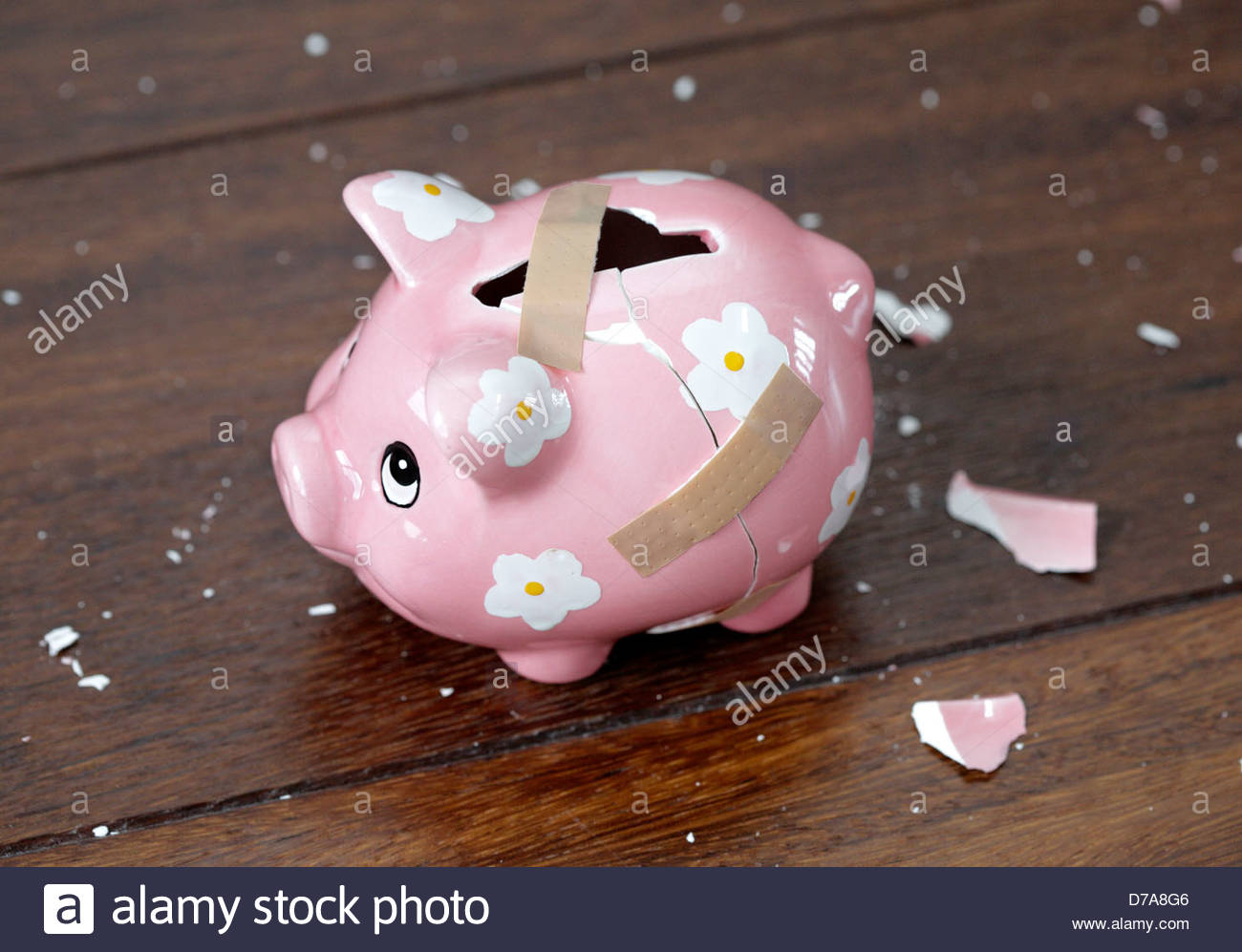 Close-up of a broken piggy bank with Bandages on it Stock Photo