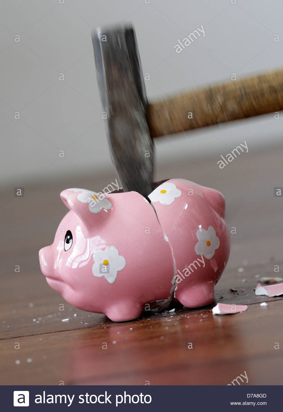 Close-up of a hammer breaking a piggy bank Stock Photo