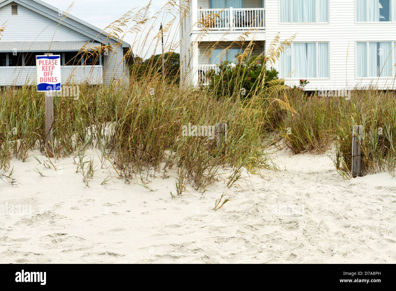A ' Please Keep Off Dunes' sign on the left with beach front houses in the background. 2 wooden post guide - Stock Image