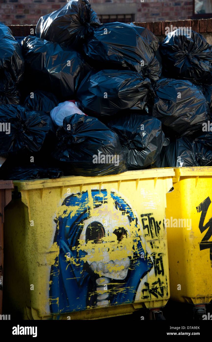 Rubbish bins overflowing black sacks commercial waste - Stock Image