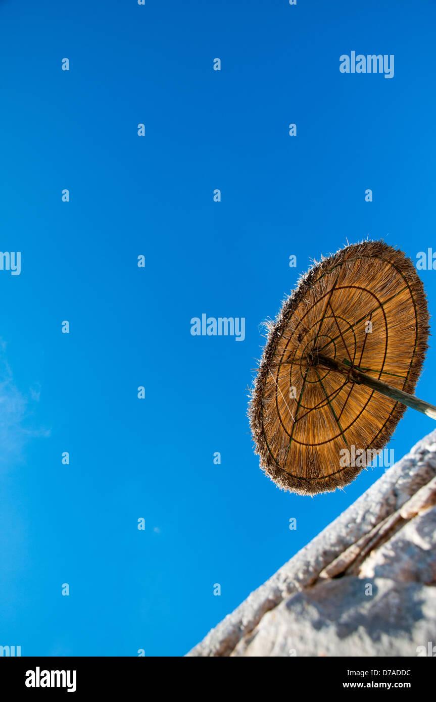 Blue sky and straw umbrella - Stock Image