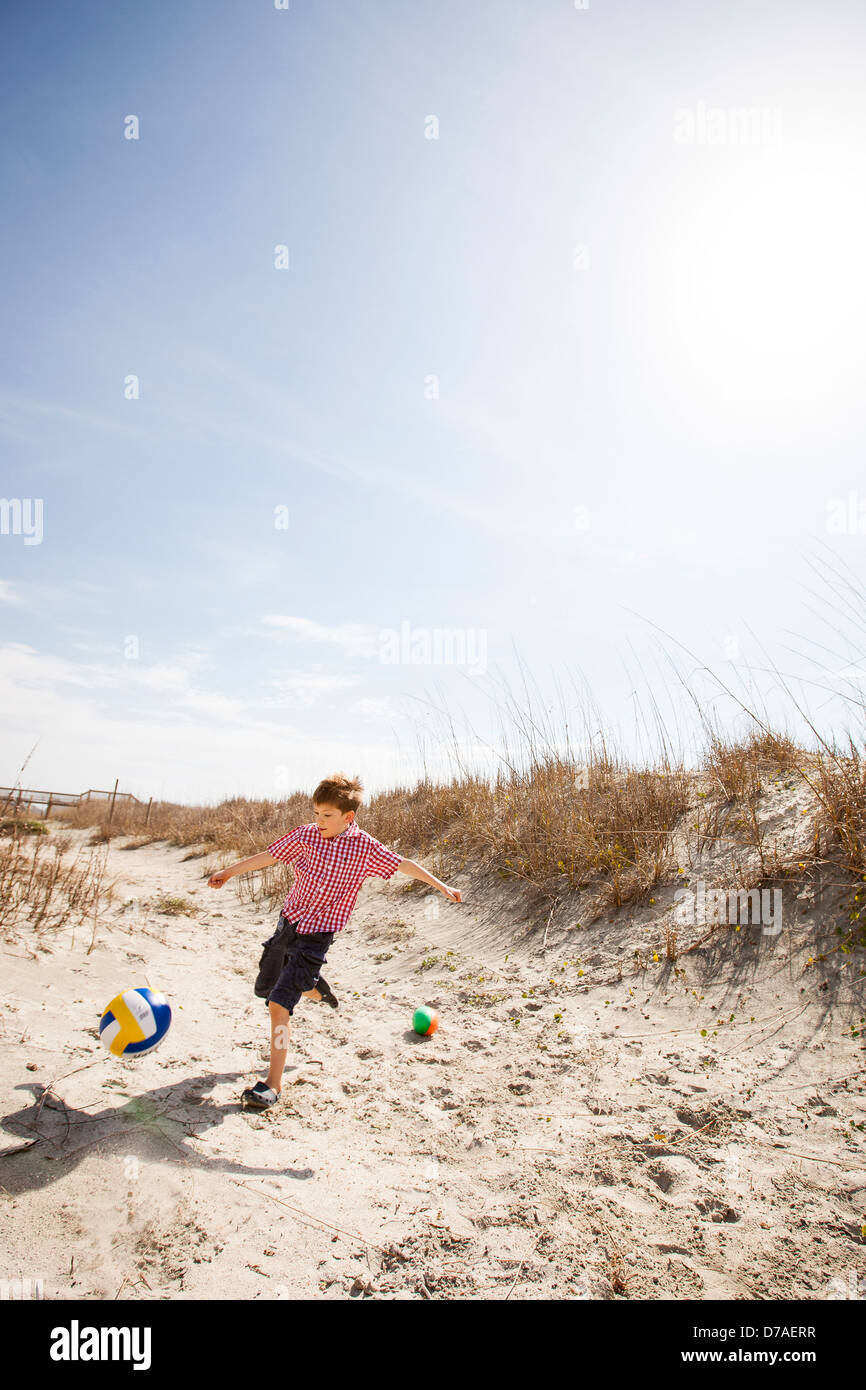 boy kicking soccer ball at beach - Stock Image