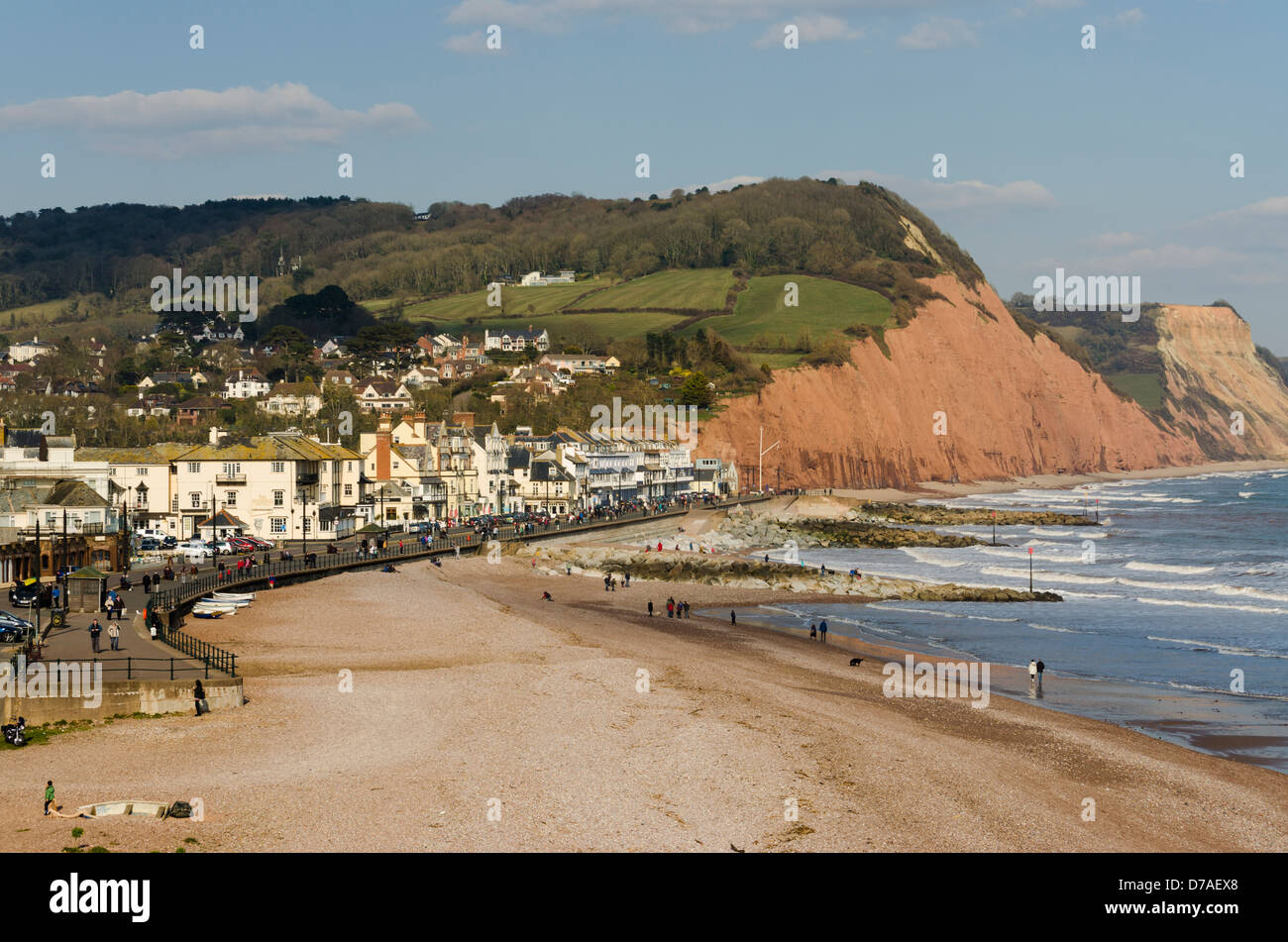 A view along Sidmouth seafront showing the beach and promenade on a sunny day. - Stock Image