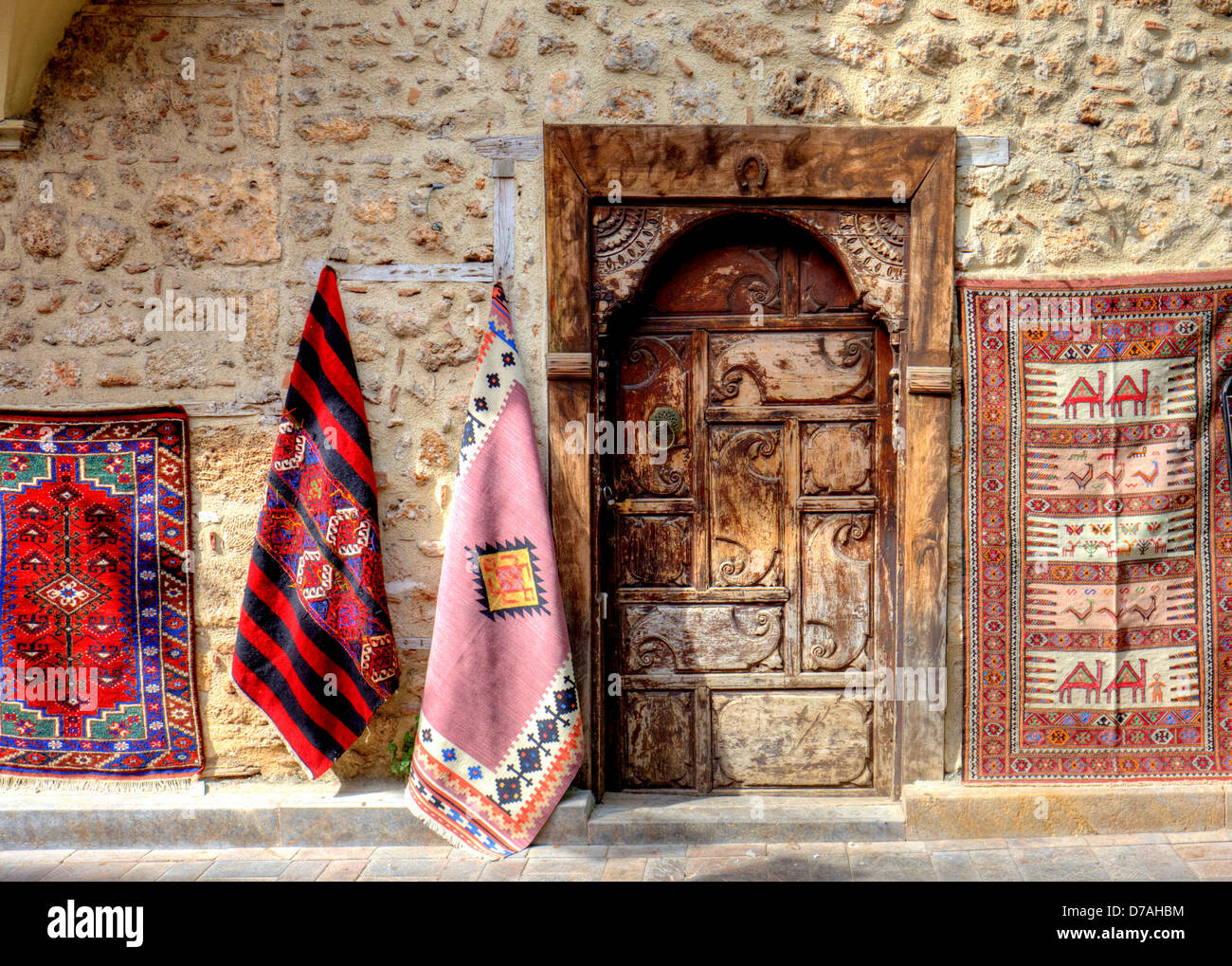Street shopping antique carpets display with old carved doorway. - Stock Image