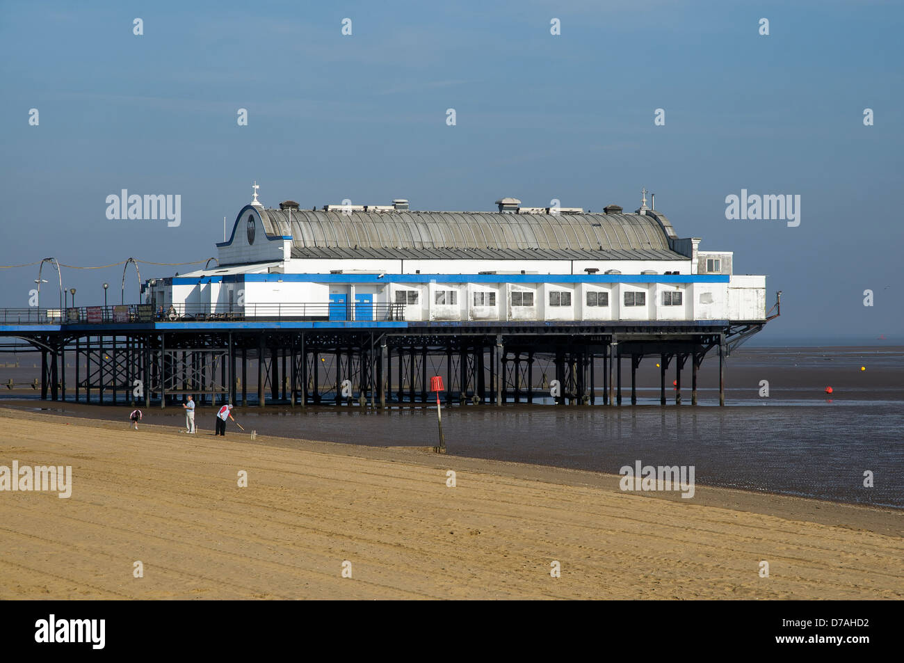 Two adults and a child play cricket on the beach in front of Cleethorpes Pier, North East Lincolnshire, United Kingdom. Stock Photo