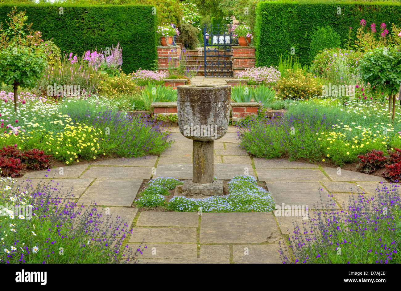Flagged formal garden with a stone vase ornament and summer flowers. - Stock Image