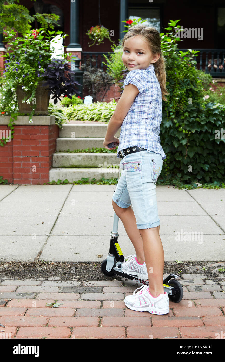 7 year old girl on scooter - Stock Image