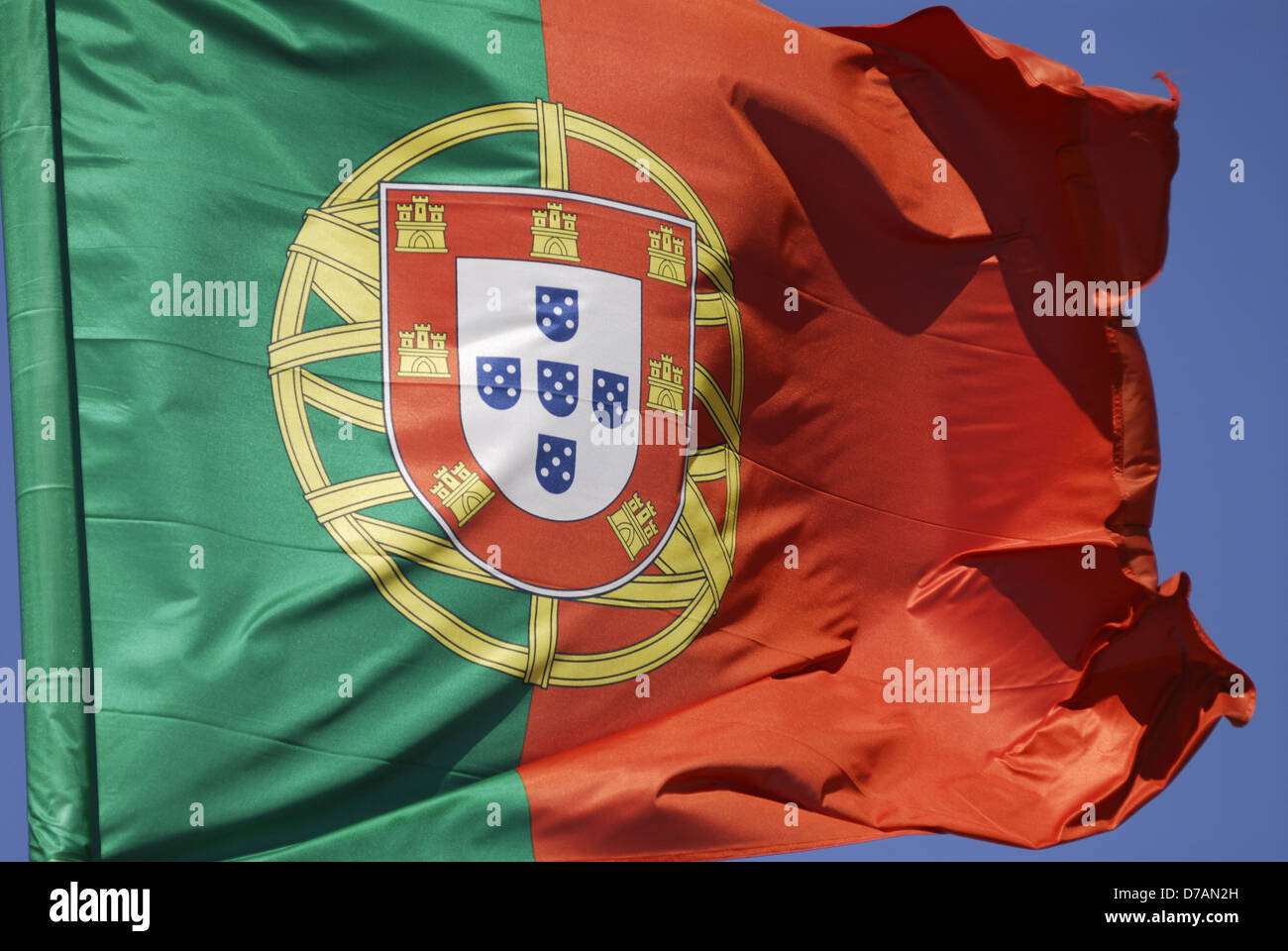 Portuguese flag blowing in the wind against blue sky Stock Photo