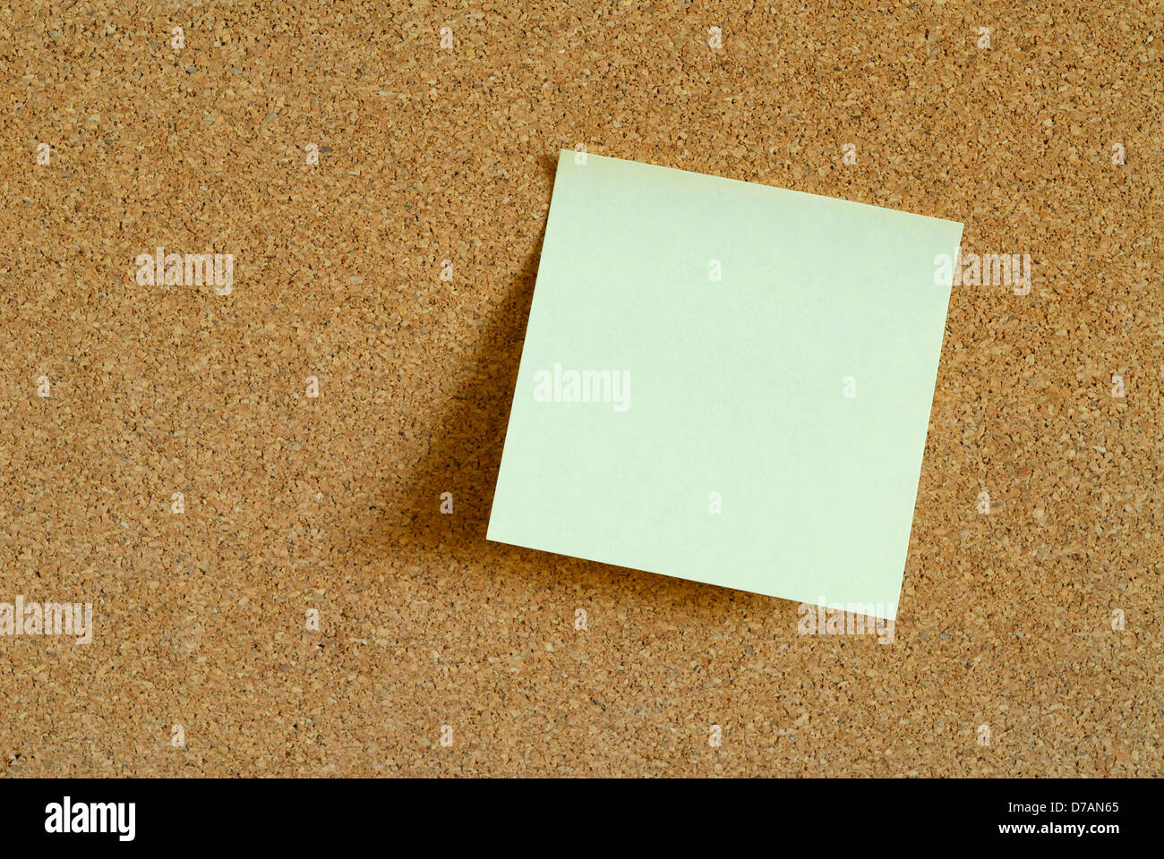 blank yellow post it memo on a cork board waiting for your message Stock Photo