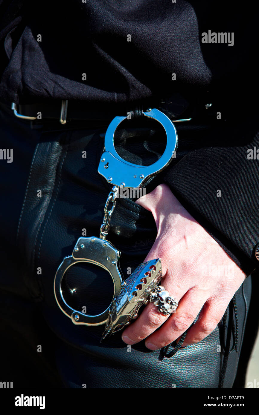 Handcuffs at the belt of a leather trouser man. - Stock Image