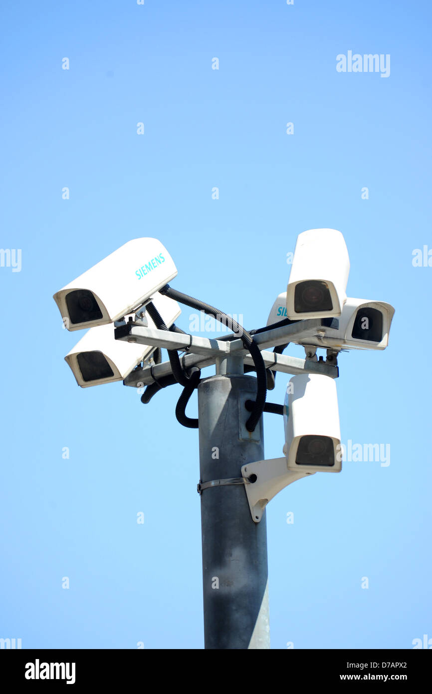 Several CCTV cameras bunched together with a blue sky background. - Stock Image