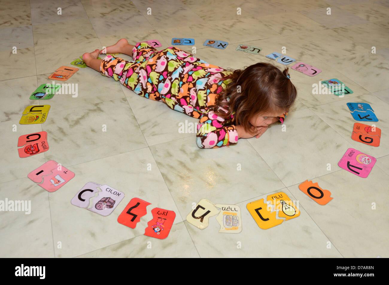 Little Jewish Israeli girl study the Hebrew alphabet at home. - Stock Image