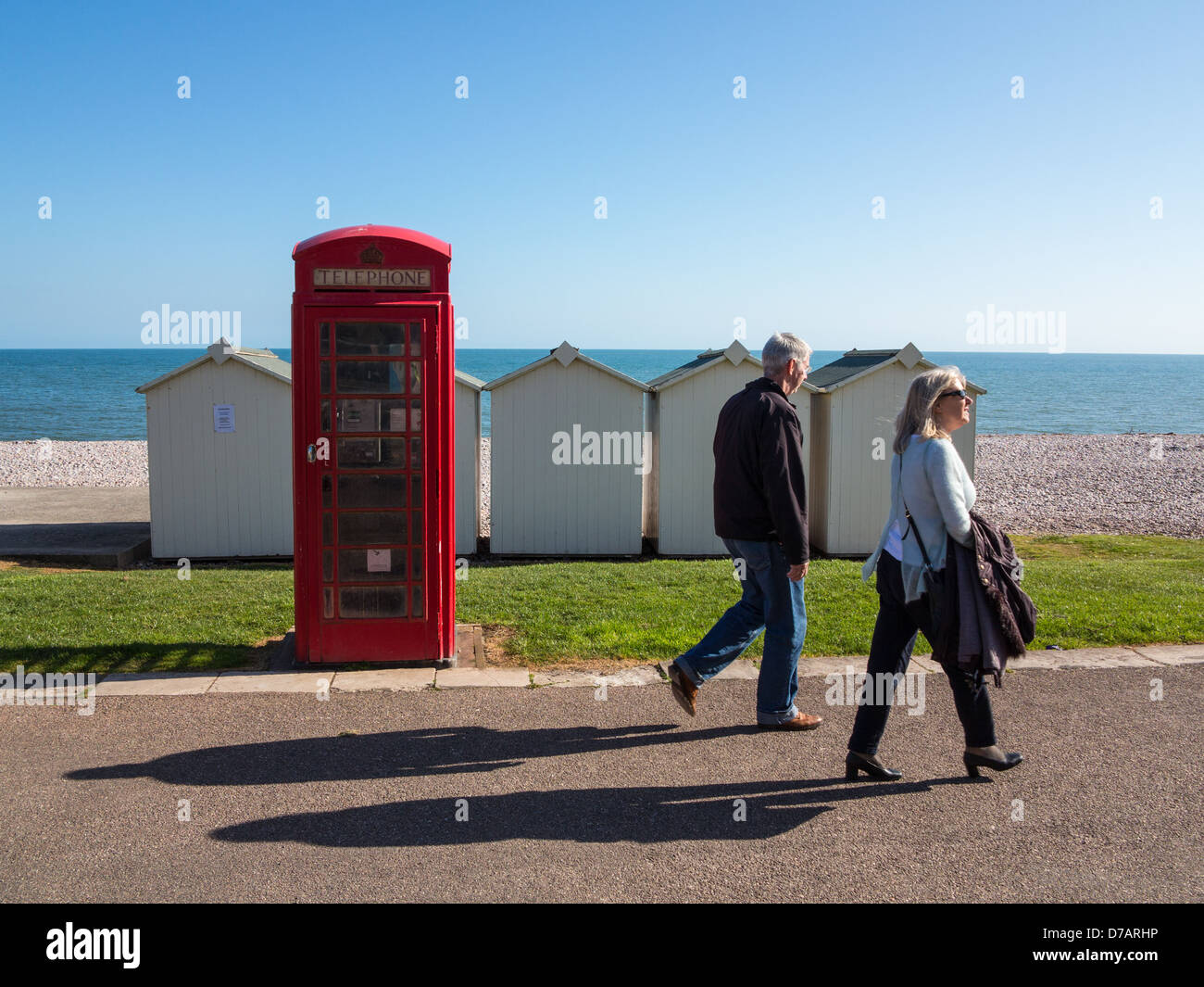 Old red telephone box and beach huts on Budleigh Salterton seafront, Budleigh Salterton, Devon, England. - Stock Image