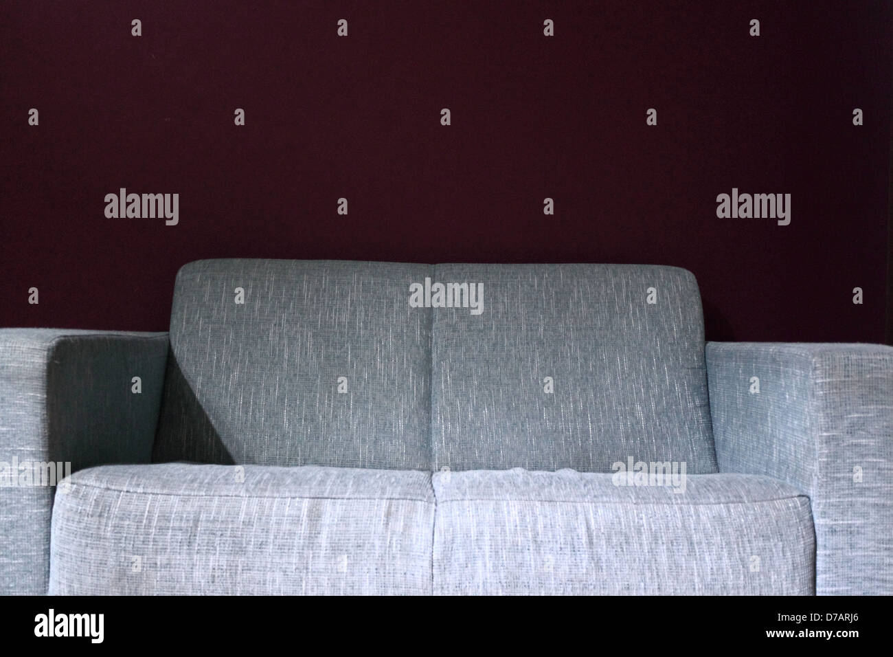 A two person blue sofa against a magenta wall - Stock Image