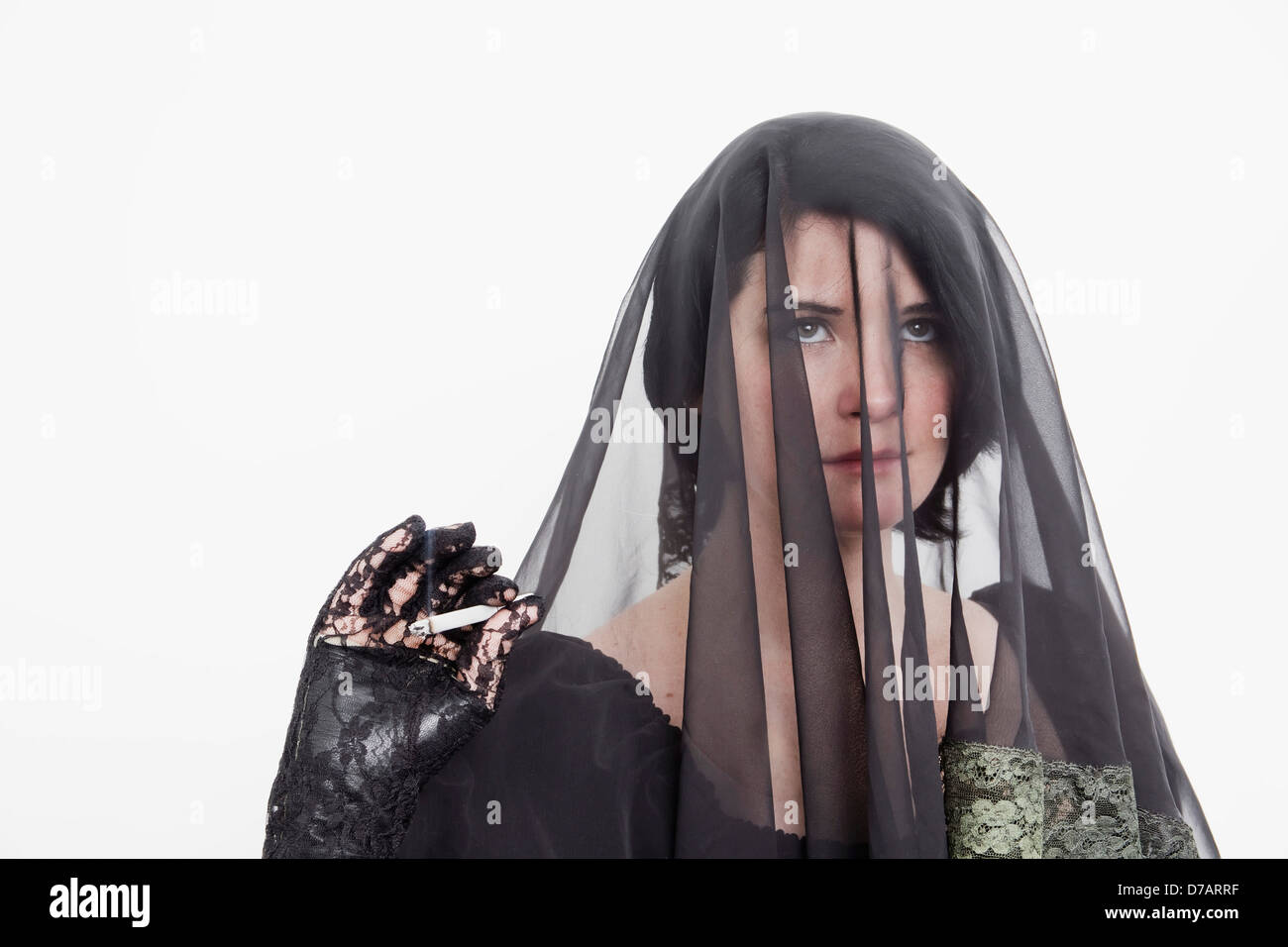 Young Veiled Woman With A Cigarette. - Stock Image