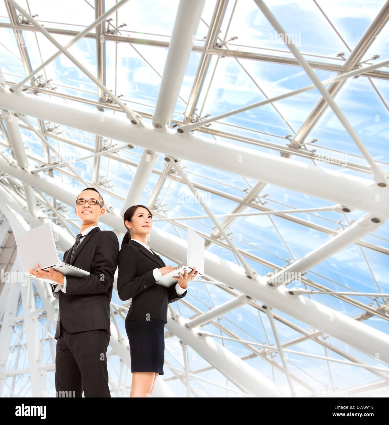 young business man and woman holding laptop and stand in the modern office - Stock Image