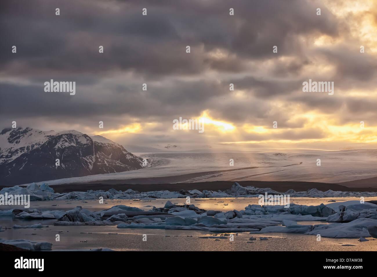 Shafts of sunlight shine on the ice calves floating in glacial lagoon jokulsarlon at the base of breioamerkurjokull; - Stock Image