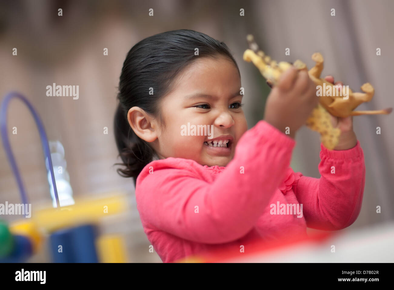 Little girl grimacing while playing rough with plastic toy animals - Stock Image