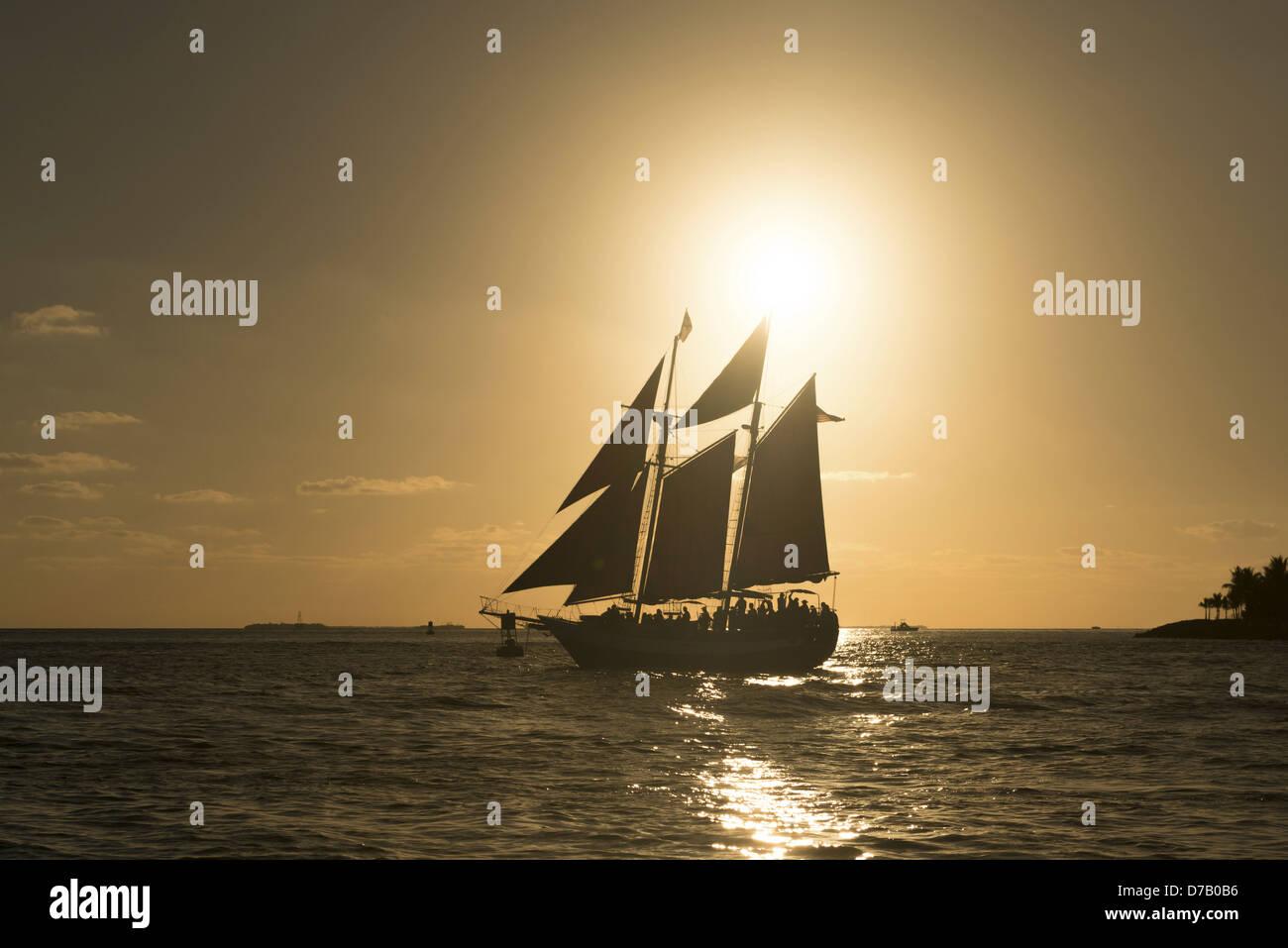 Saling ship in front of sunset, Key West, Florida Keys, Florida, USA - Stock Image