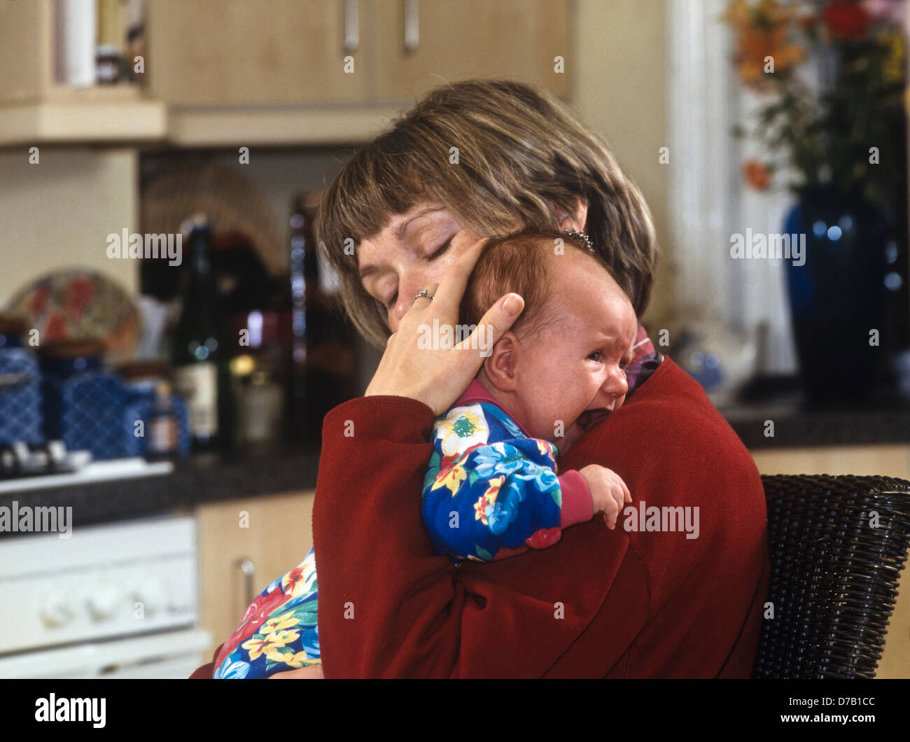 Mother cuddling crying baby (6 weeks old) in the kitchen - Stock Image