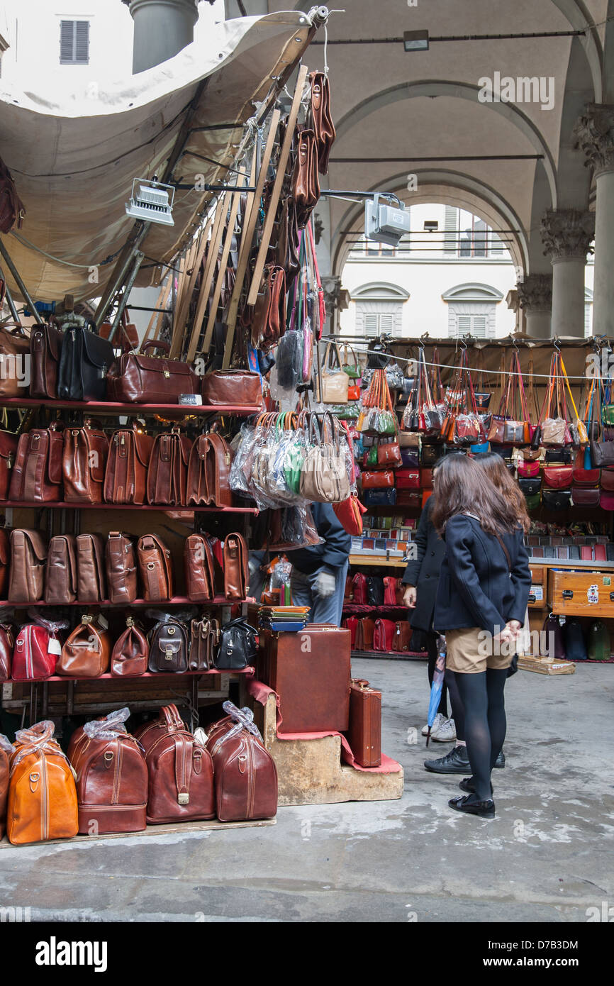Female Tourists looking at Leather Bags in Mercato Nuovo - New Market; Florence; Italy - Stock Image