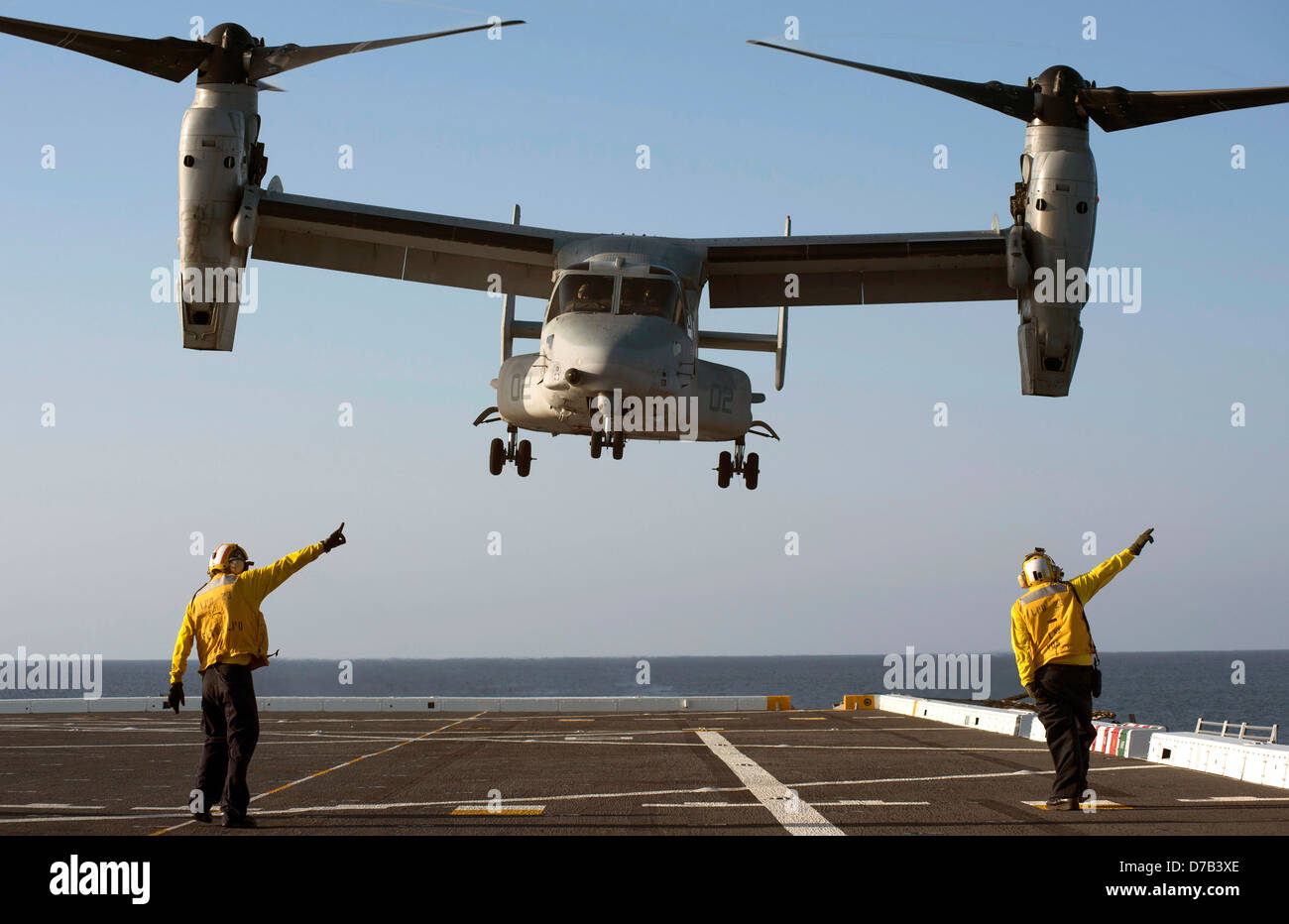 US Navy Aviation Boatswains Mates directs the launch of an MV-22 Osprey tilt rotor aircraft on the flight deck of - Stock Image