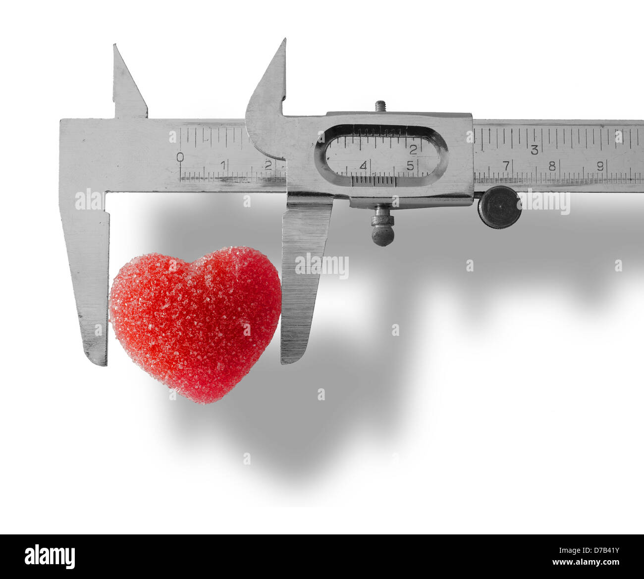 Heart measured with caliper. Isolted over white background - Stock Image