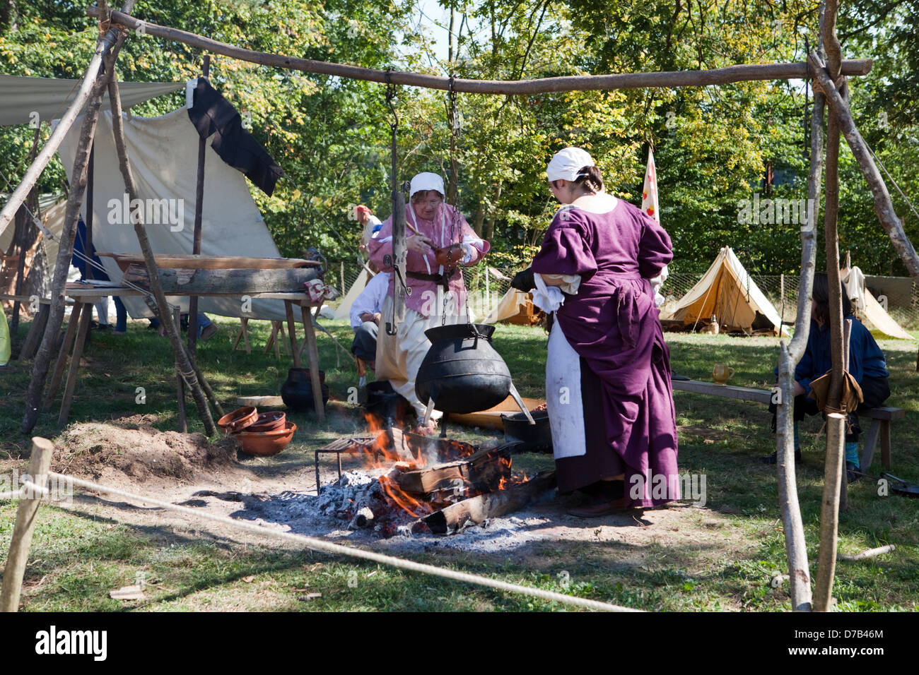 Women with a cooking pot over a campfire, live role-playing in front of the Musée d'Art Moderne Grand-Duc - Stock Image