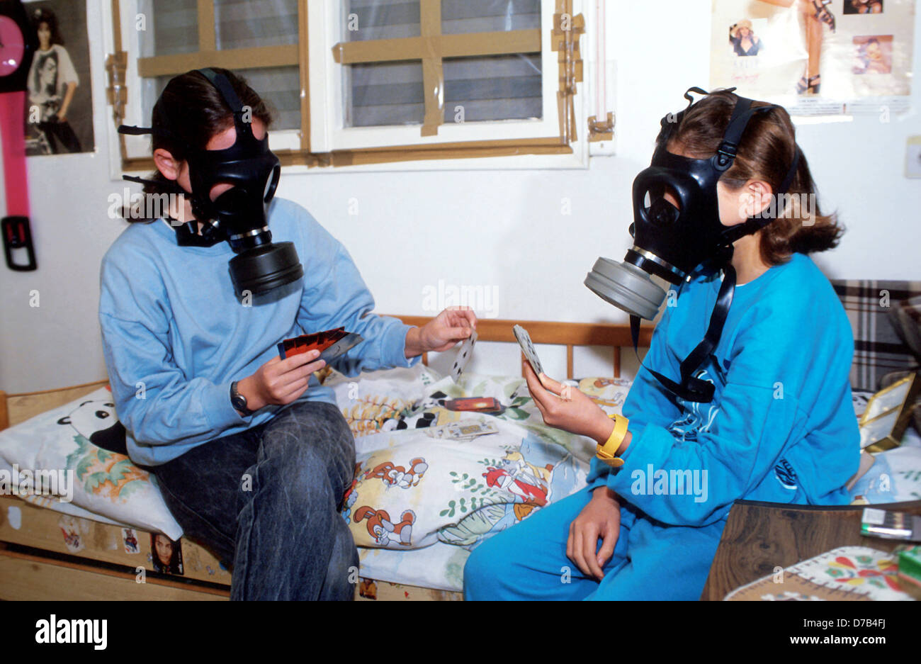 sisters wearing gas masks at the gulf war - Stock Image