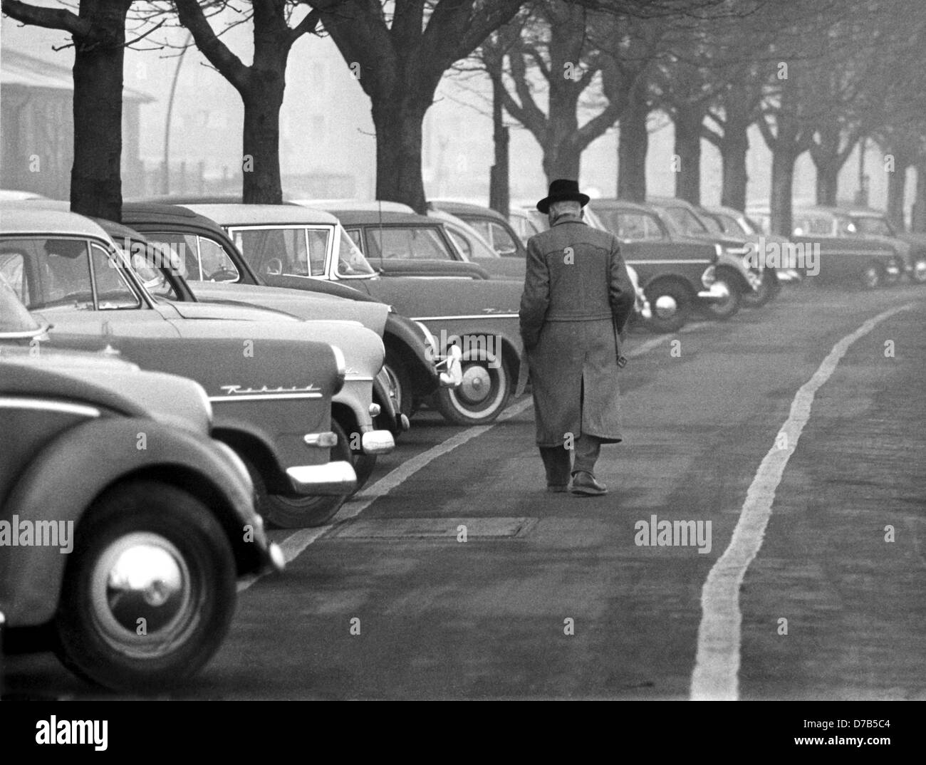 A pedestrian walks past a row of parked cars, photographed on the 20th of March in 1961 in a German city. Stock Photo