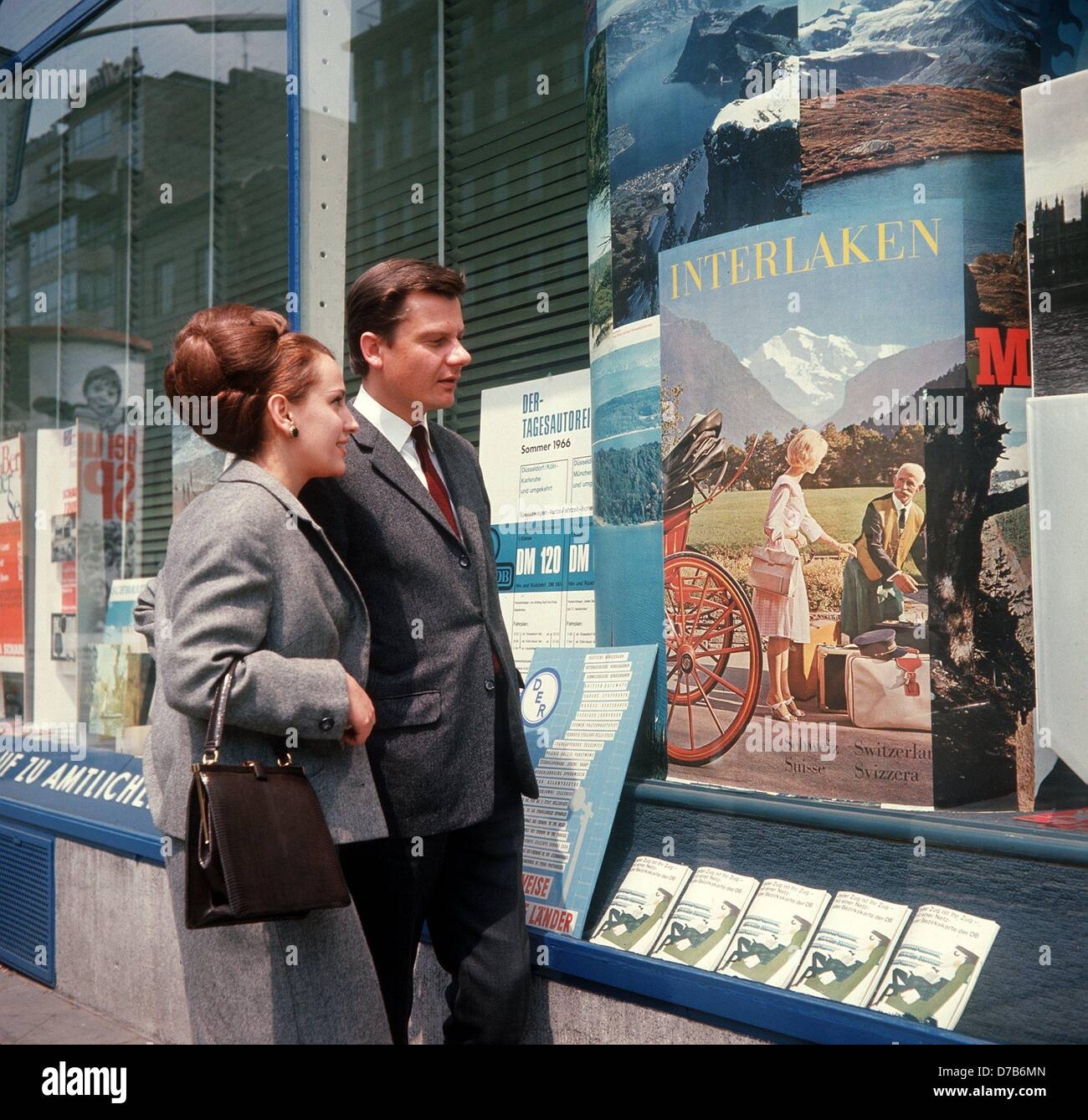 A young couple has a look at a poster advertising for the Swiss town Interlaken in the window shop of a travel agency (picture from the 1960s). Stock Photo