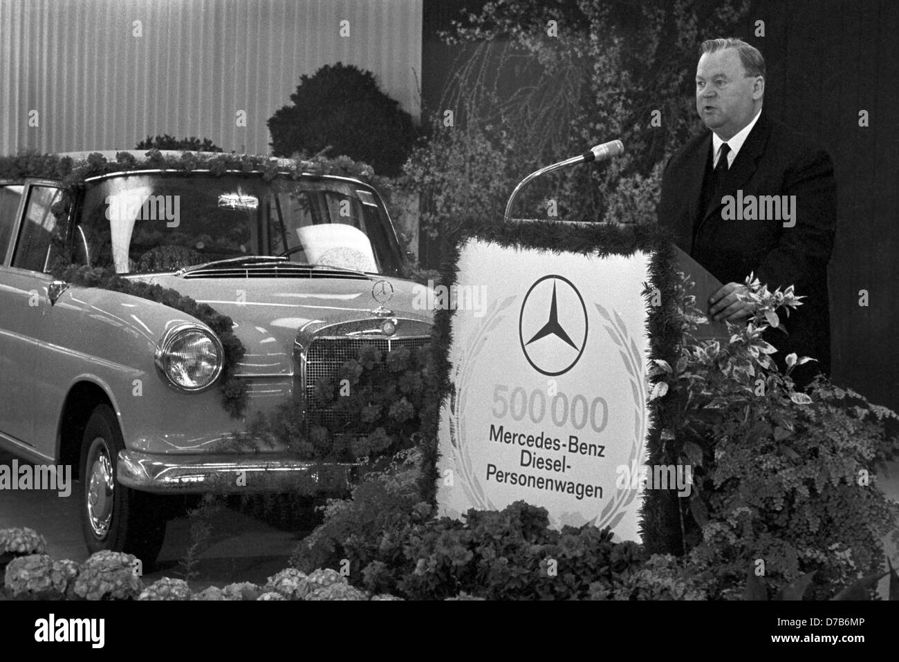 Daimler-Benz general director Walter Hitzinger is giving a speech on the 500,000th Mercedes-Benz Diesel car, on 8 April 1965, in Sindelfingen. On the left, the anniversary wagon from the assembly plant in Sindelfingen. Stock Photo
