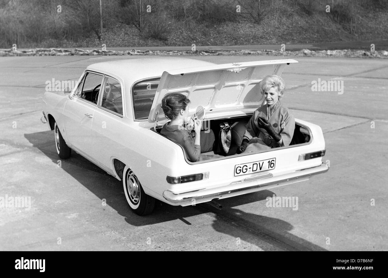 """The new Opel """"Rekord"""" is presented in Ruesselsheim on the 5th of February in 1963. The picture shows two women sitting in the trunk of the new Opel to illustrate the car's spaciousness. Stock Photo"""