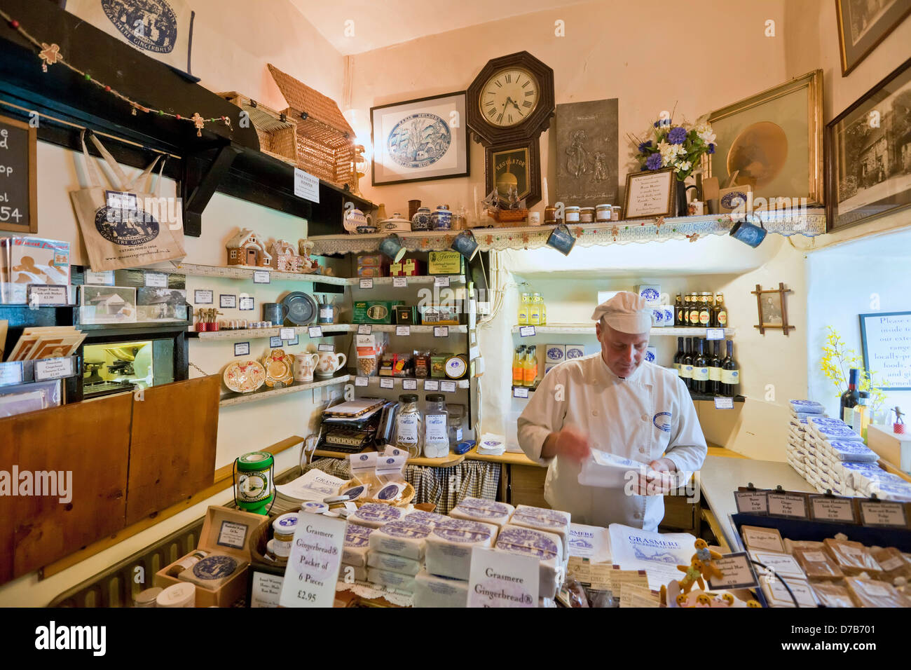 Man working inside the Grasmere gingerbread shop, a traditional biscuit cake made on the premises Grasmere Village - Stock Image