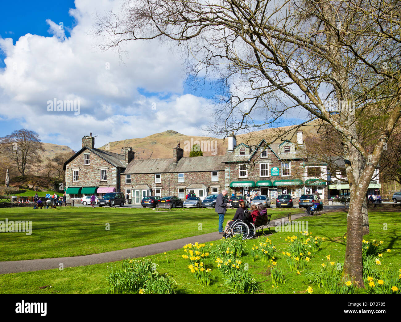 People sat on benches around the village green enjoying the spring sunshine  in Grasmere Cumbria England UK GB EU - Stock Image