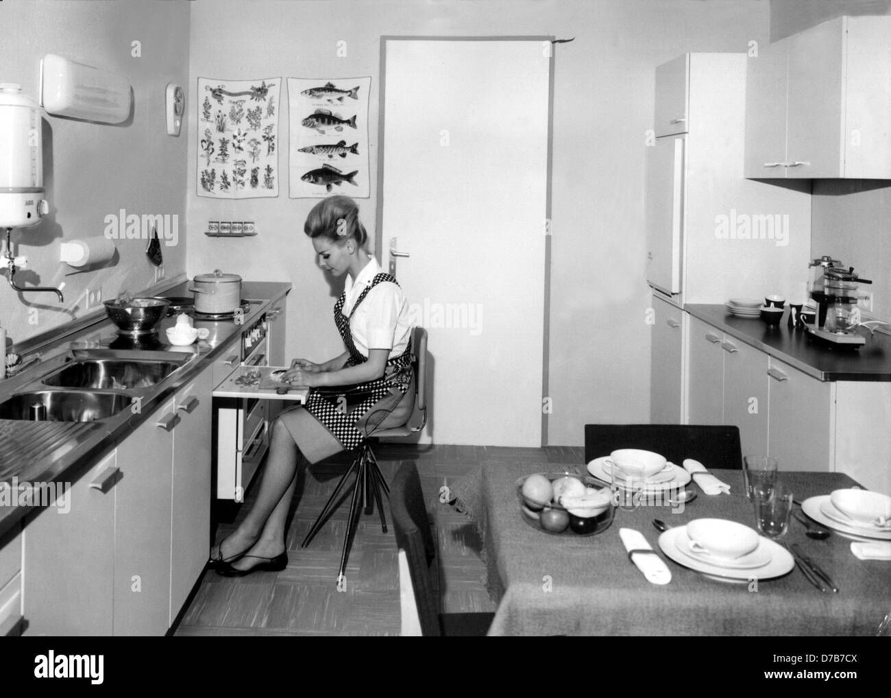 A housewife can prepare her vegetables at an extendible worktop while sitting. This ergonomic kitchen was ultra modern in the 1960s. Stock Photo