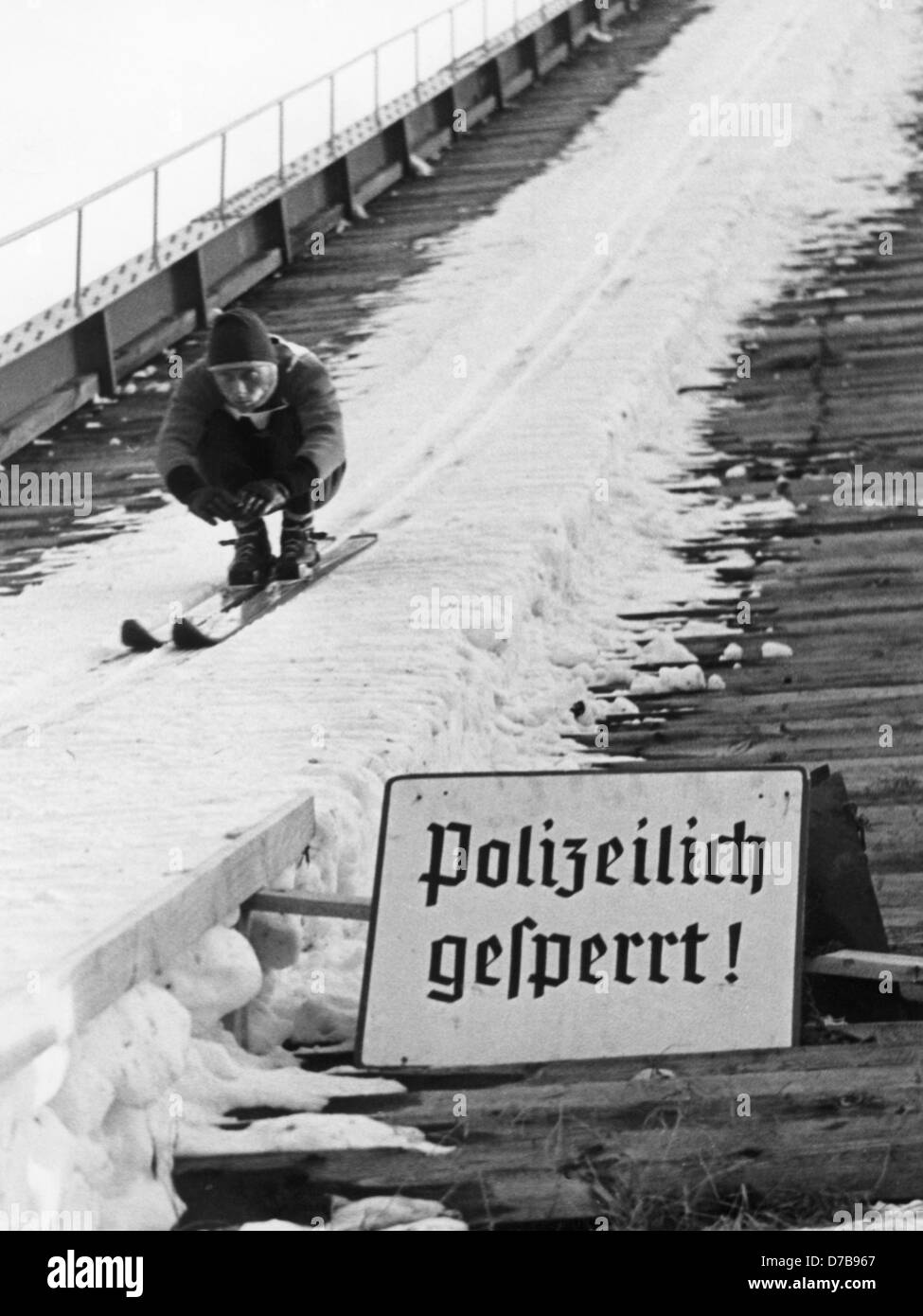 """Despite the sign saying """"Closed by the police"""", Max Bolkart sets for his jump of eighty metres on the """"Grosse Olympiaschanze"""" in Garmisch-Partenkirchen at the traditional New Years tournament in 1957. The police ban certainly did not affect the professionals. Stock Photo"""