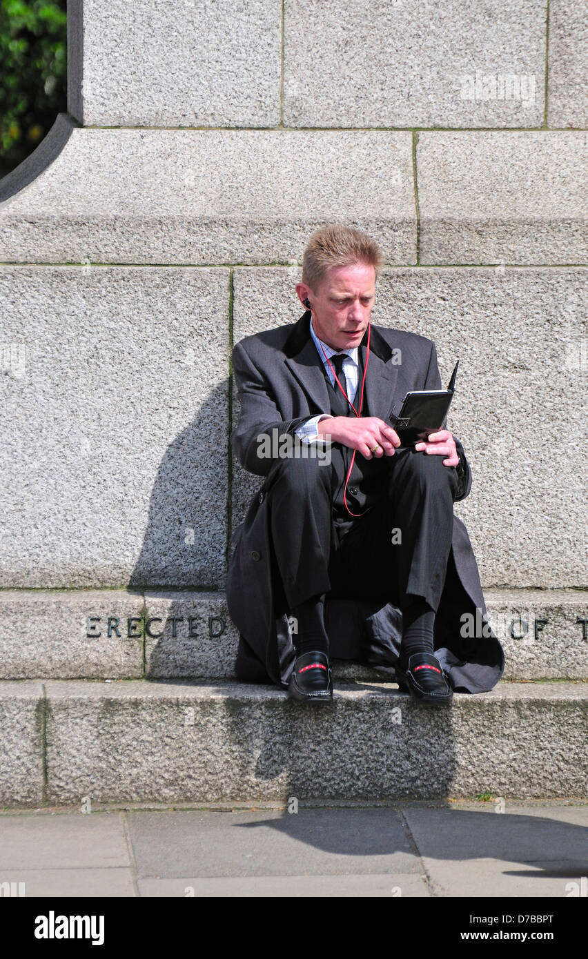 London, England, UK. Man in a suit sitting and reading an ebook - Stock Image
