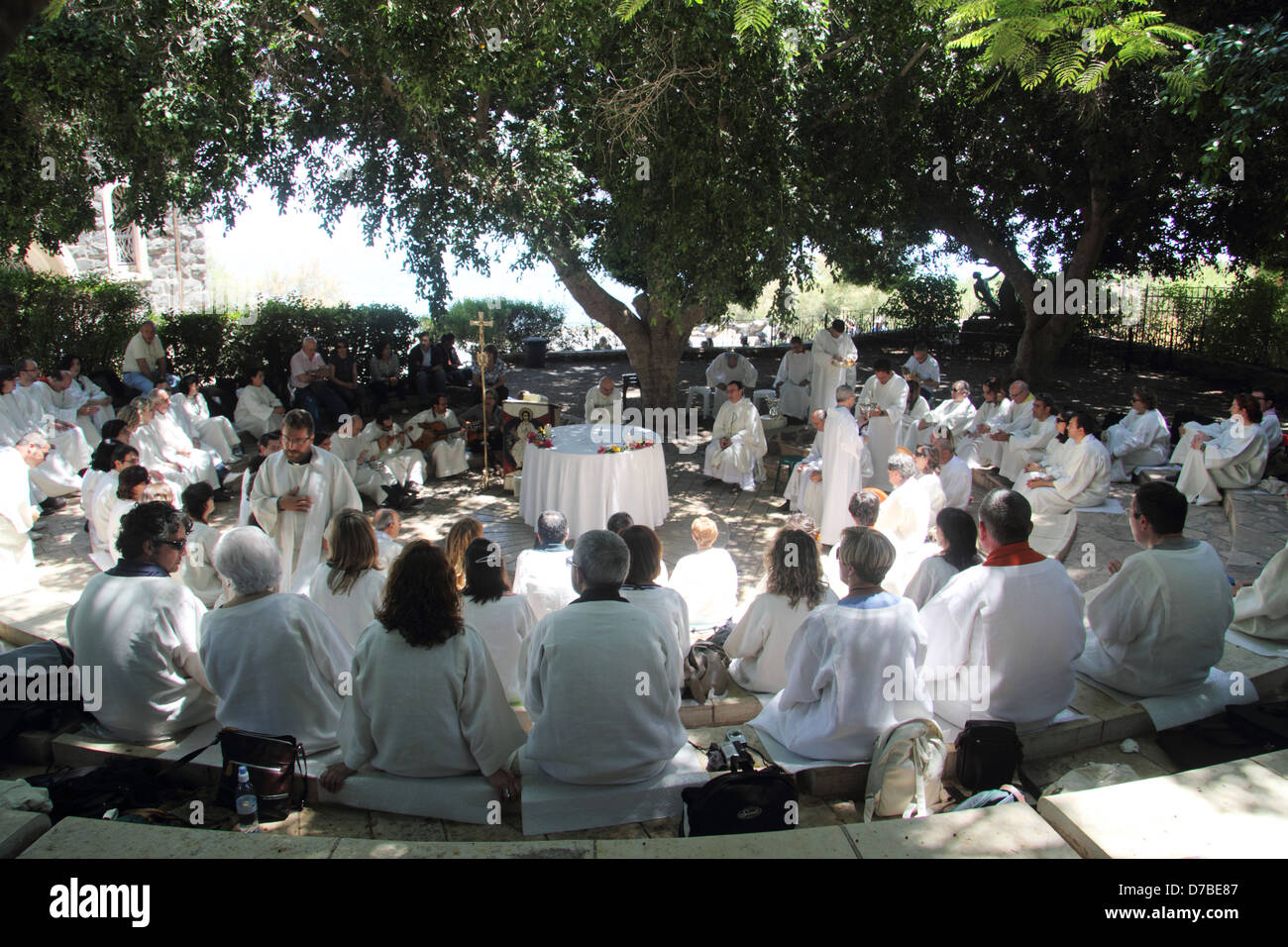 Christian Spanish pilgrims pray by The Church of the Primacy of Peter at Tabgha by the Sea of Galilee - Stock Image
