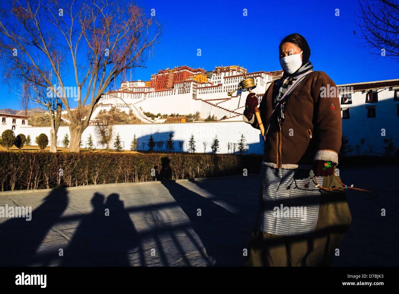 Pilgrim Tibetan woman walking the Kora around Potala palace. Lhasa, Tibet - Stock Image