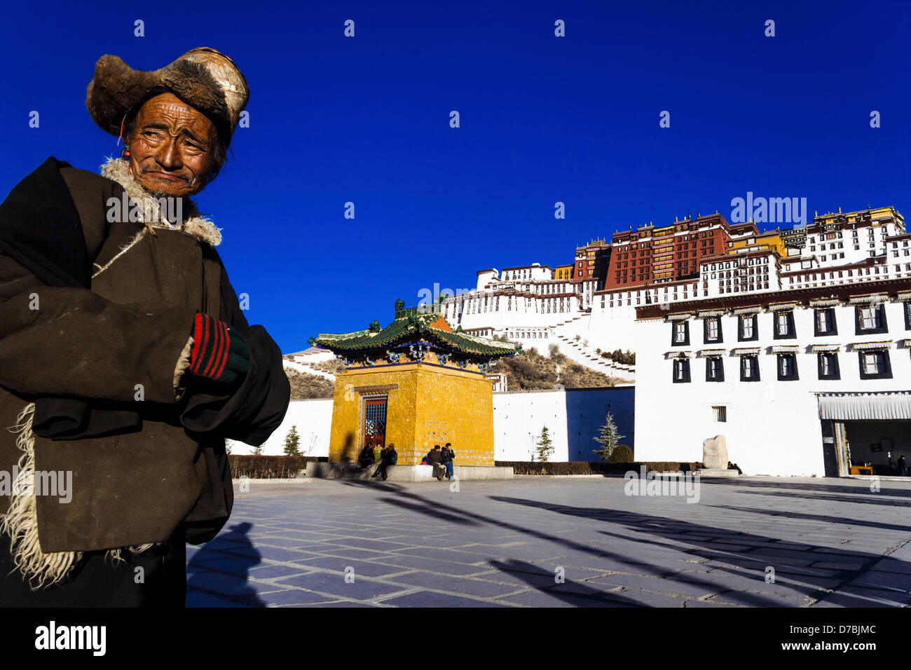 Old Tibetan man with fur hat standing in front of Potala palace in Lhasa, Tibet, China - Stock Image