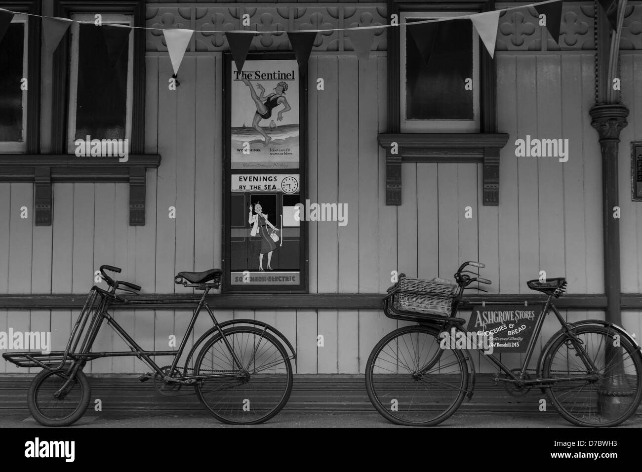 A monochrome image of a station building on the Bluebell Railway showing adverts and two old push bikes. - Stock Image