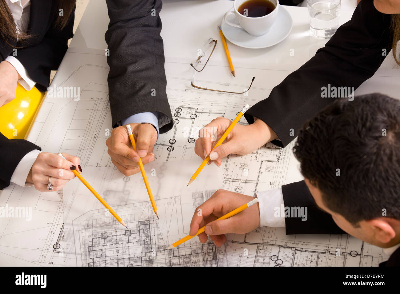 Businesspeople working together at meeting, discussing document - Stock Image
