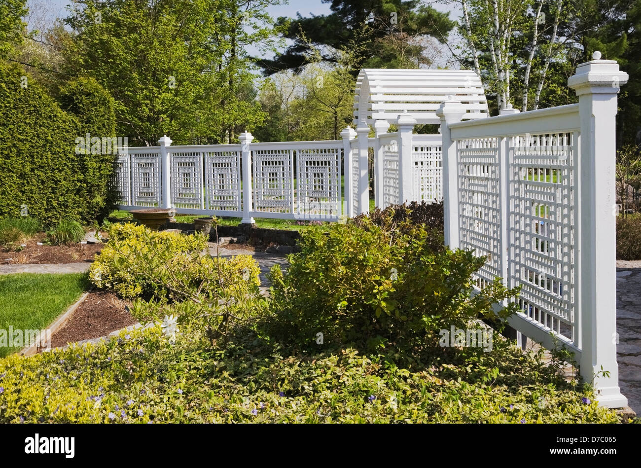 A White Wooden Fence With Trellis In A Landscaped Back Yard Garden In  Spring;Quebec Canada