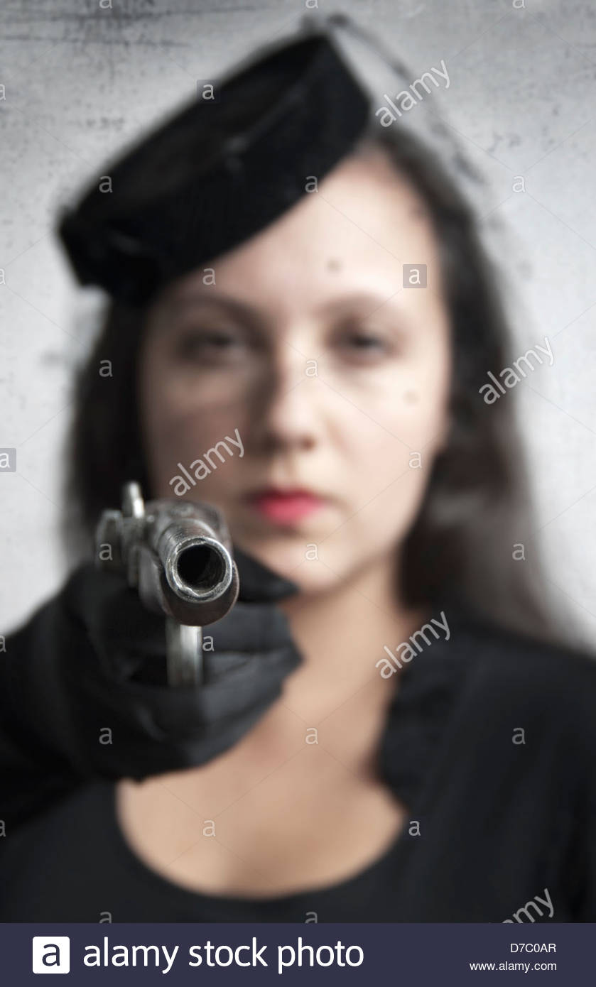 Woman in vintage hat and veil and wearing black gloves is pointing an old pistol, gun is in focus - Stock Image
