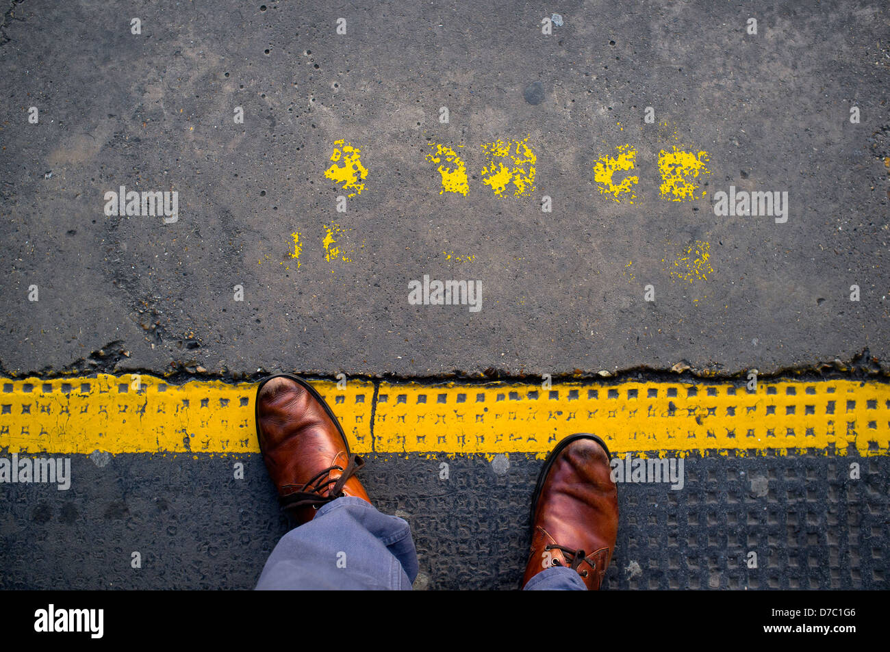 Man standing on train platform yellow safety line - Stock Image