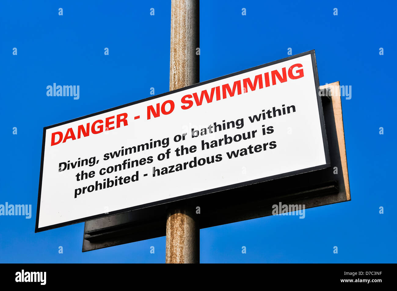 Sign at a harbour warning against swimming due to hazardous waters - Stock Image