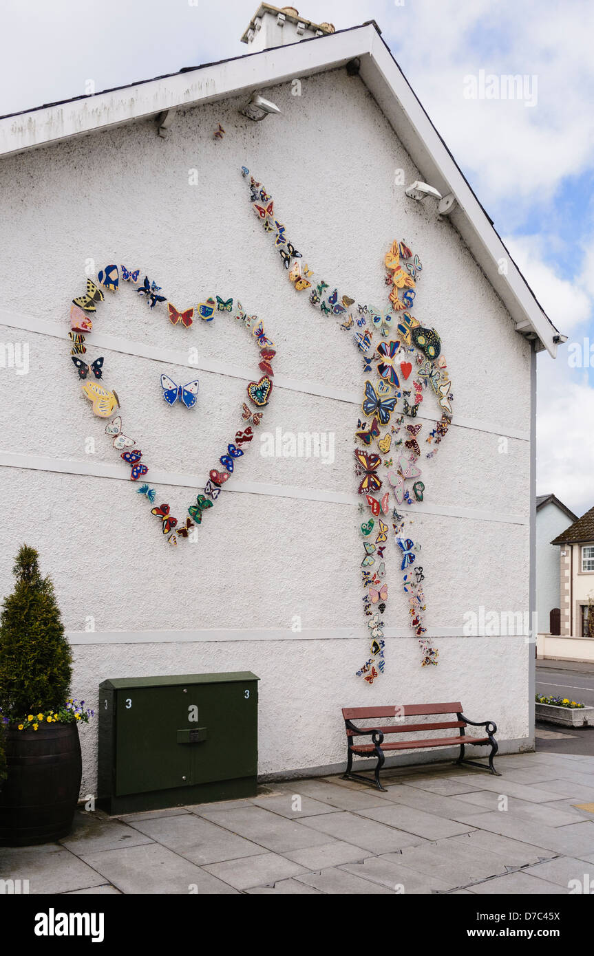 Ceramic butterflies, made by local school children, on a wall in Broughshane village making up a person and a heart. - Stock Image