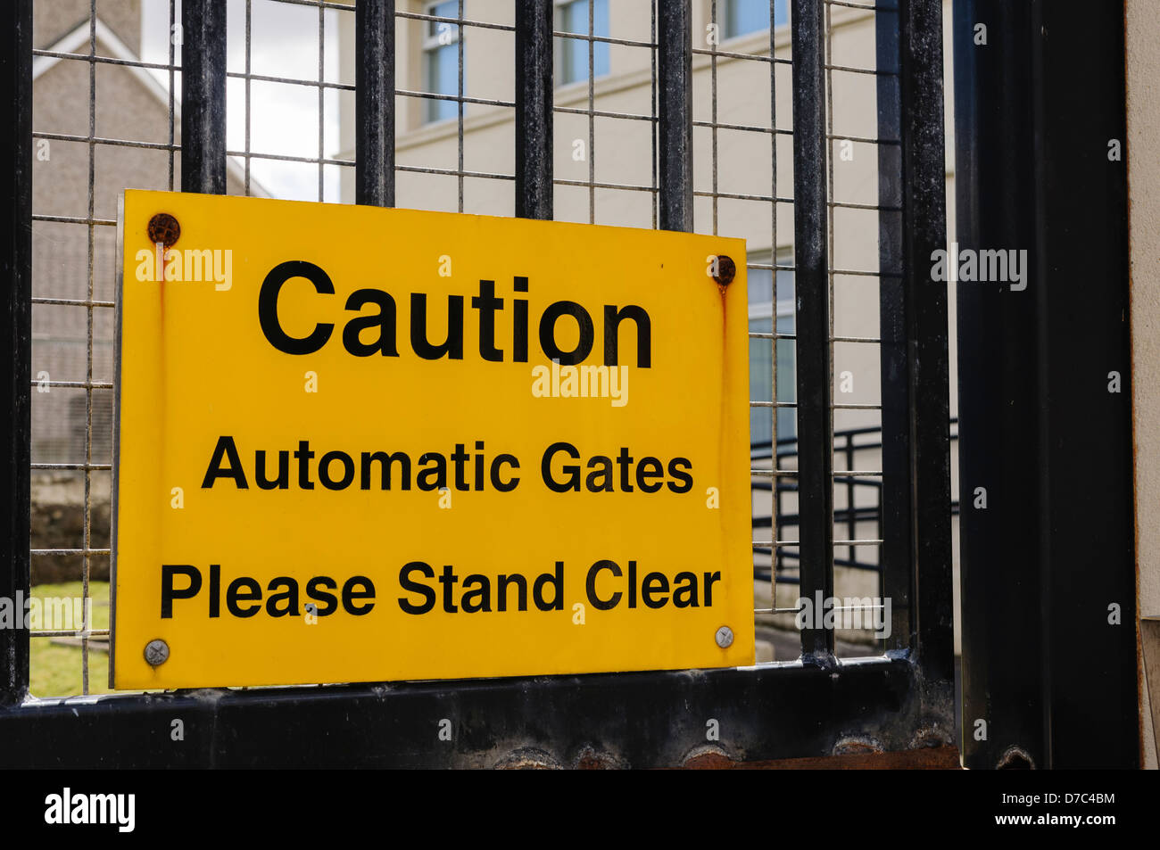 Sign at a heavily fortified PSNI police station 'Caution: automatic gates. Please stand clear' - Stock Image