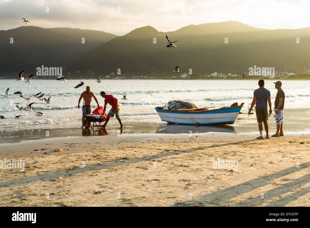 Fishermen and fishing boat on the sand at Pantano do Sul Beach. - Stock Image